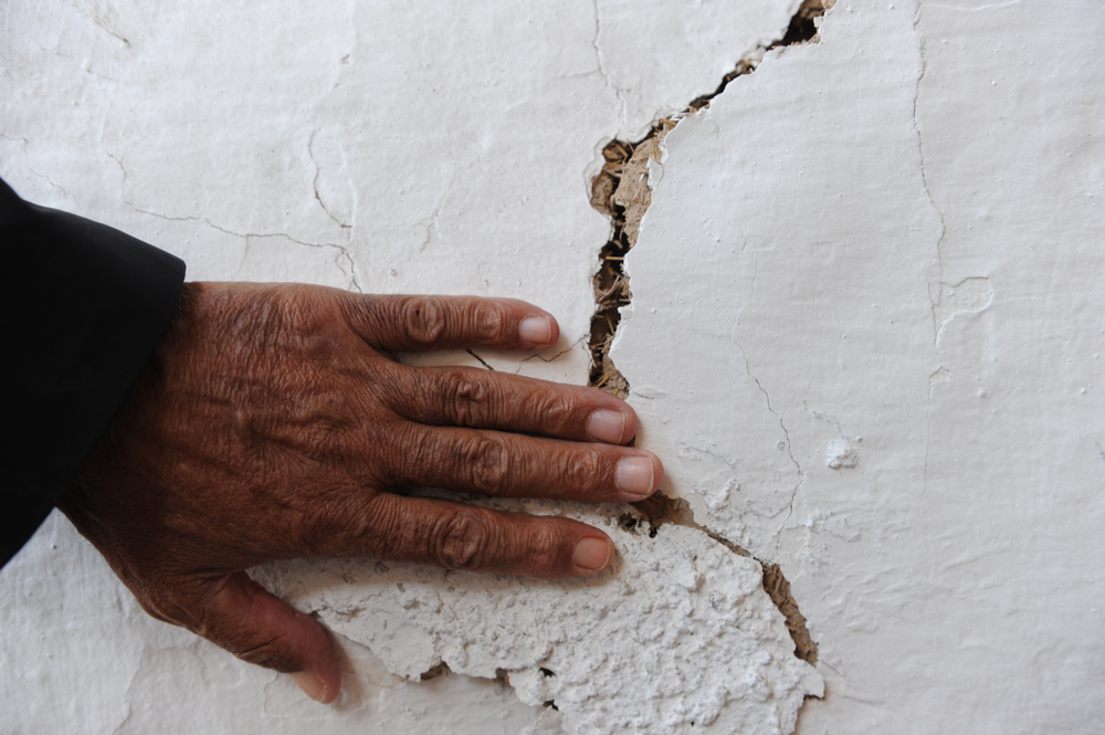 Hand on cracked wall
